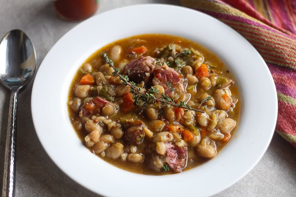white bean stew with ham hocks in a bowl