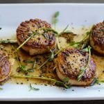 pan-seared scallops on plate topped with herbs and coffee vinaigrette