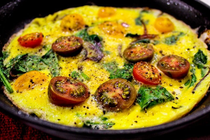 Open Face spinach Omelet in black skillet