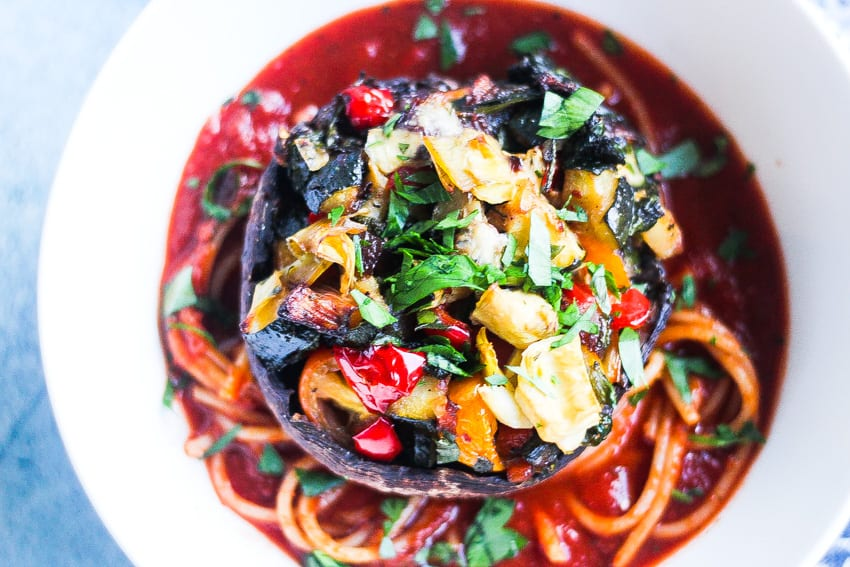 a bowl of spaghetti with pasta sauce topped with a whole portobello mushroom stuffed with vegetables
