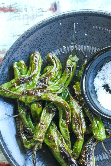 blistered shishito peppers on a black plate