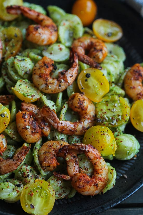 baby kale pesto pasta with spicy shrimp on a plate.