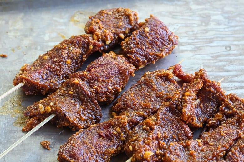 beef suya skewers raw on pan