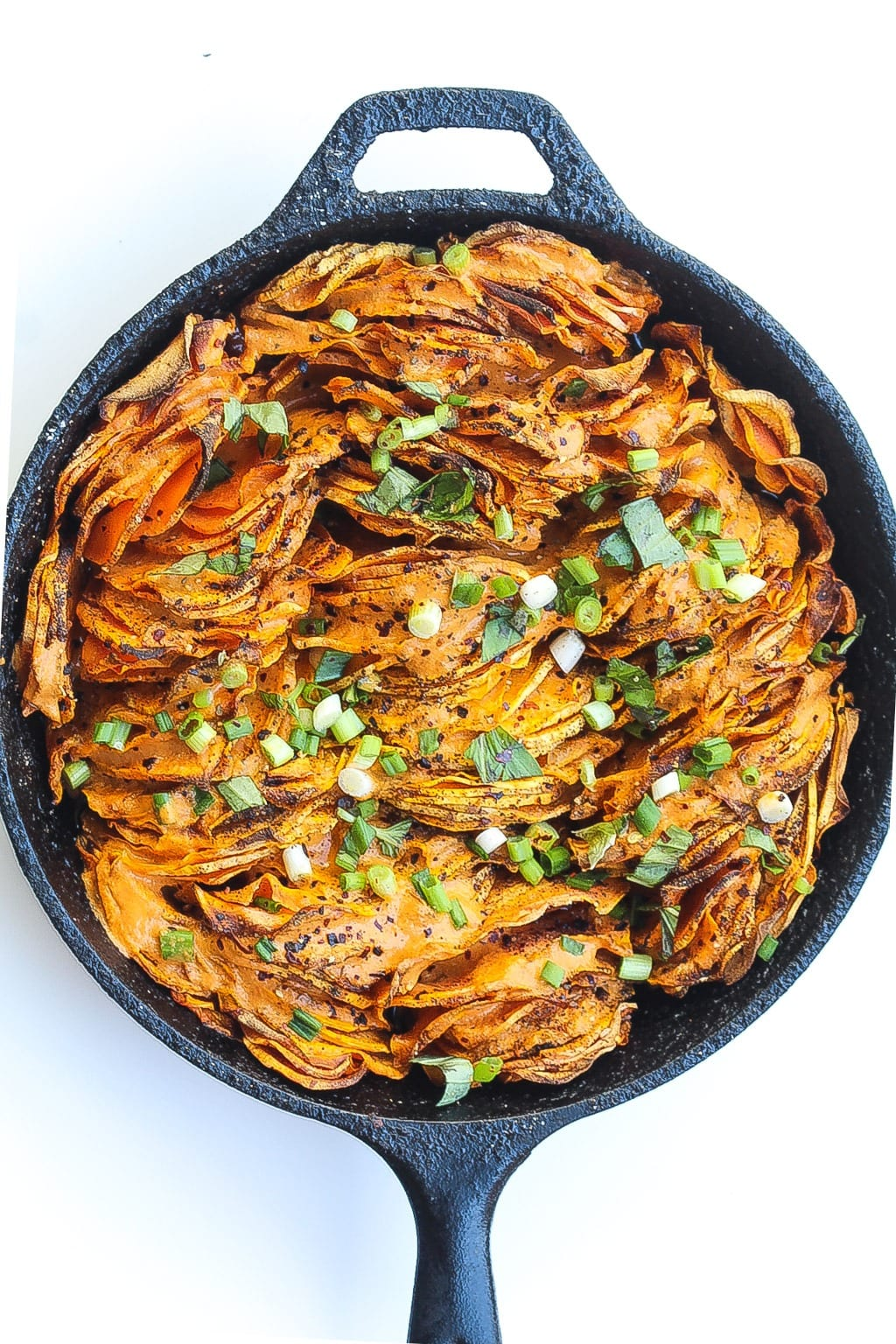 hasselback sweet potatoes in a skillet topped with green onions and red pepper sauce