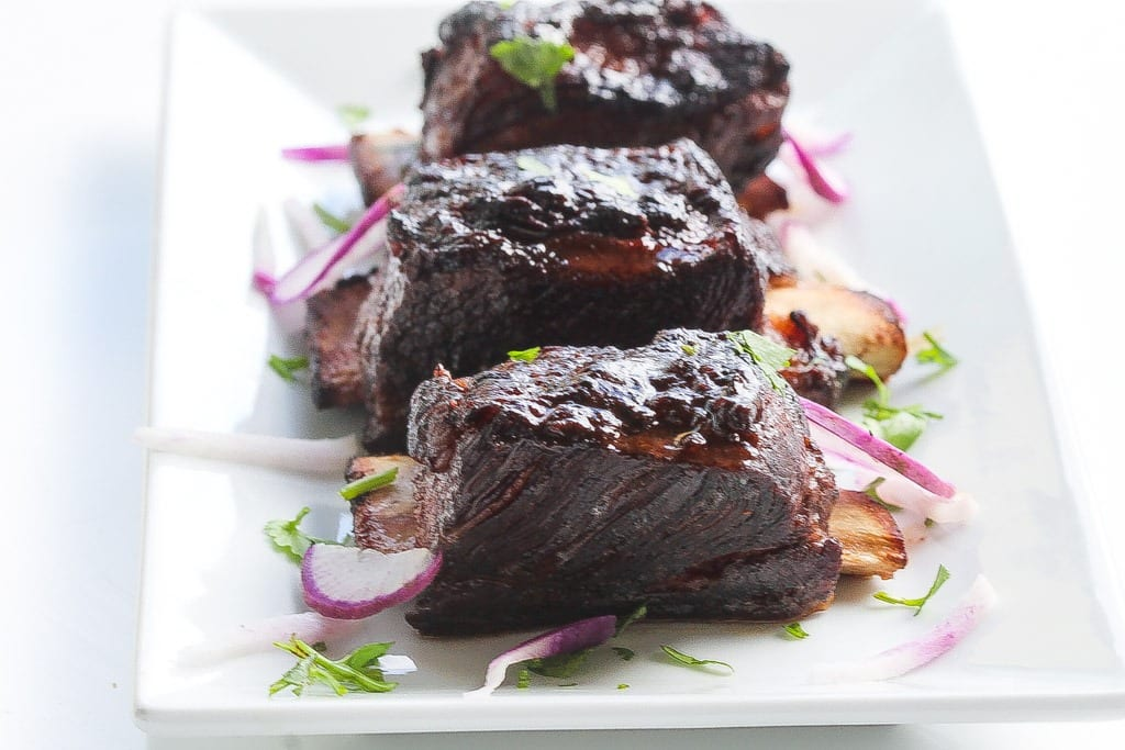 sous vide short ribs glazed and on a plate with purple daikon and cilantro