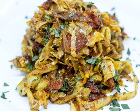 indian fried cabbage on a white plate with tomatoes and fresh herbs